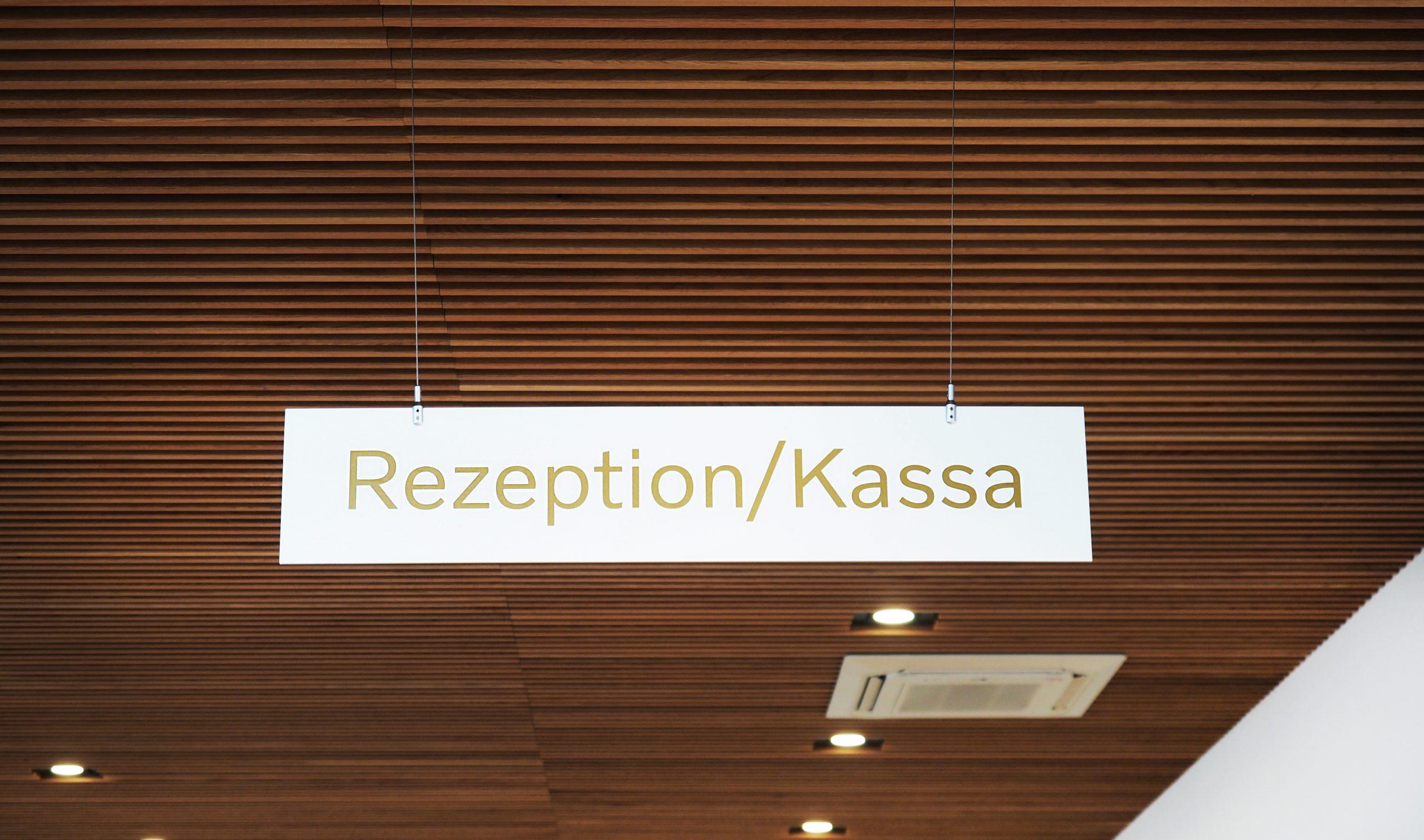 Schild mit Schriftzug Rezeption/Kassa